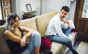 Young couple sitting on sofa being angry after fight.