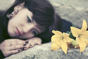 Sad young woman with flowers lying on a large rock